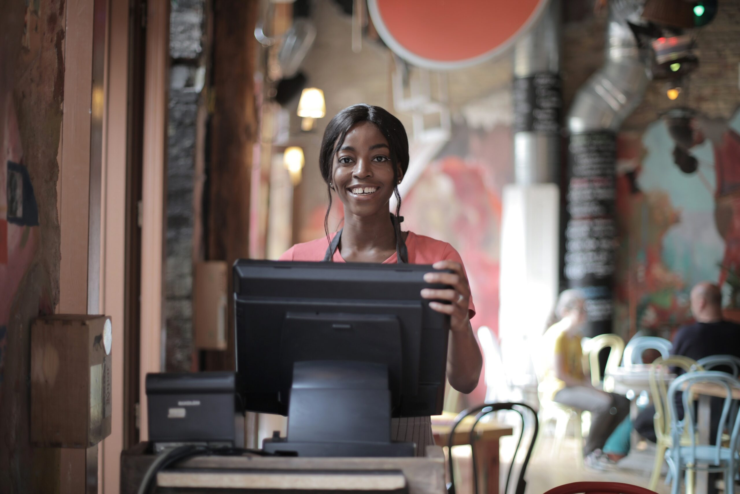 Cheerful black waitress standing at counter 3801426 scaled
